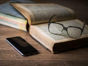 Open book with reading glasses and iPhone